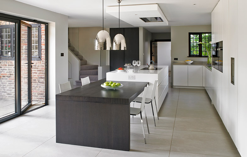 Wimbledon Kitchen Design sleek white modern cabinets and island, dark oak dining table