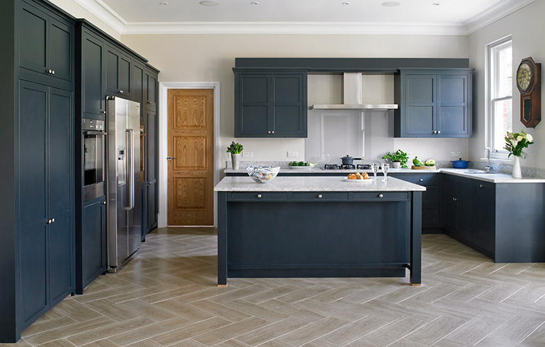 Traditional, dark blue shaker style kitchen with grey herringbone floor and light walls.
