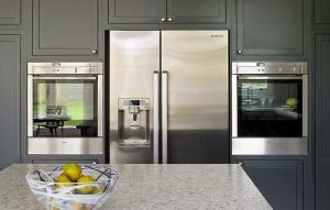 Large American Fridge Freezer and stainless steel wall mounted appliances for Dark Esher kitchen design