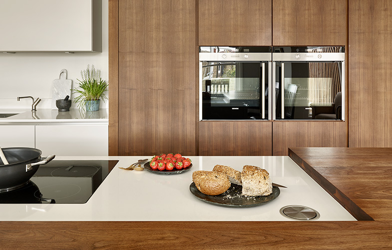 Split level island with integrated hob and breakfast bar. Walnut cabinets with wall-mounted double oven.