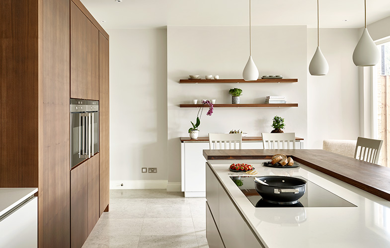 Cornforth White and Walnut kitchen design Wimbledon - teardrop pendants, integrated hob and ovens and split level island and breakfast bar.