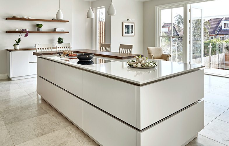 Wimbledon Kitchen design with handle-less island storage and breakfast bar. Glass doors out through to balcony.