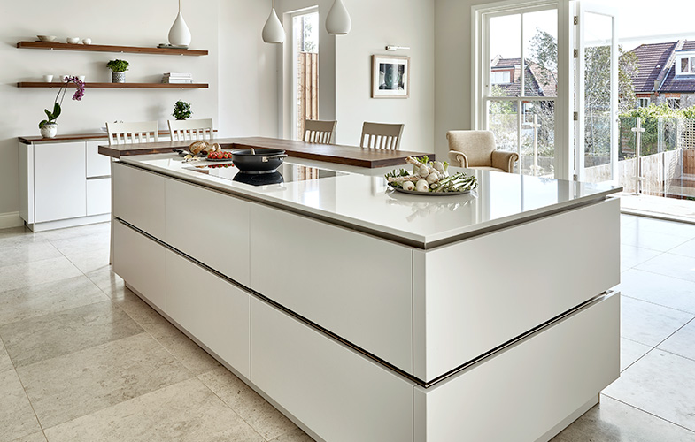 New Wimbledon Kitchen design with handle-less island storage and breakfast bar. Glass doors out through to balcony.