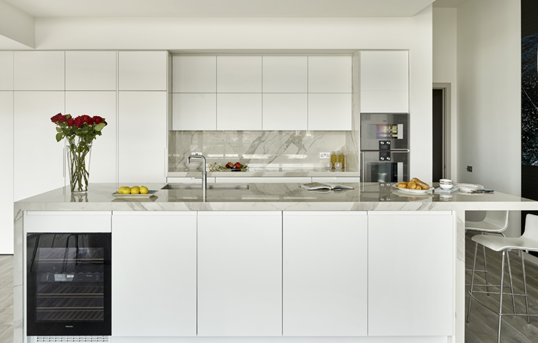London penthouse kitchen design with matt white lacquer cabinets and Laminam Staturio effect marble worktops