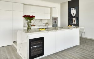 Side front view of kitchen and island with integrated wine fridge for Wandsworth modern penthouse renovation