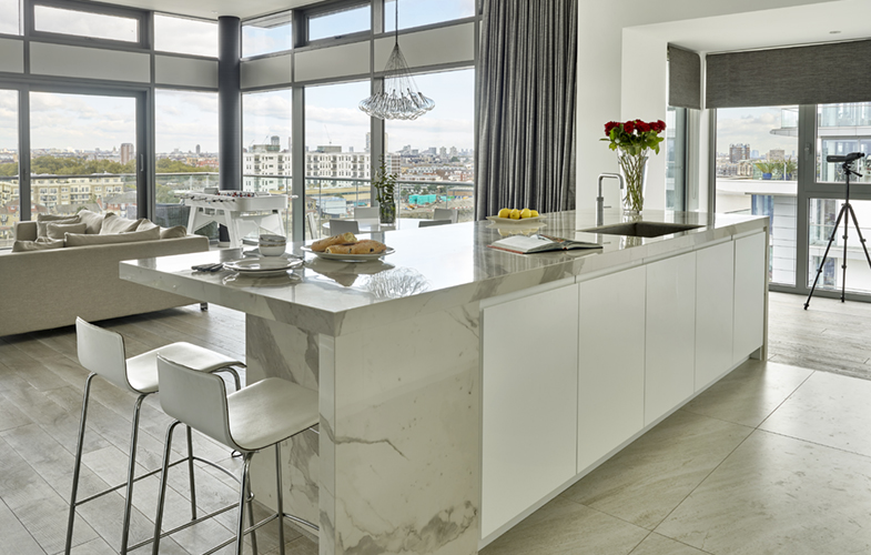 Contemporary open plan London riverside penthouse apartment with matt white lacquer and Laminam Staturio effect marble island