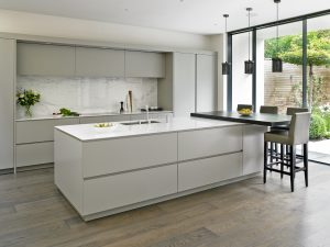 Brayer Contemporary Minimalist Kitchen design in Wandsworth with grey handleless kitchen cabinets and white countertops. Island with raised breakfast bar and custom bar stools.