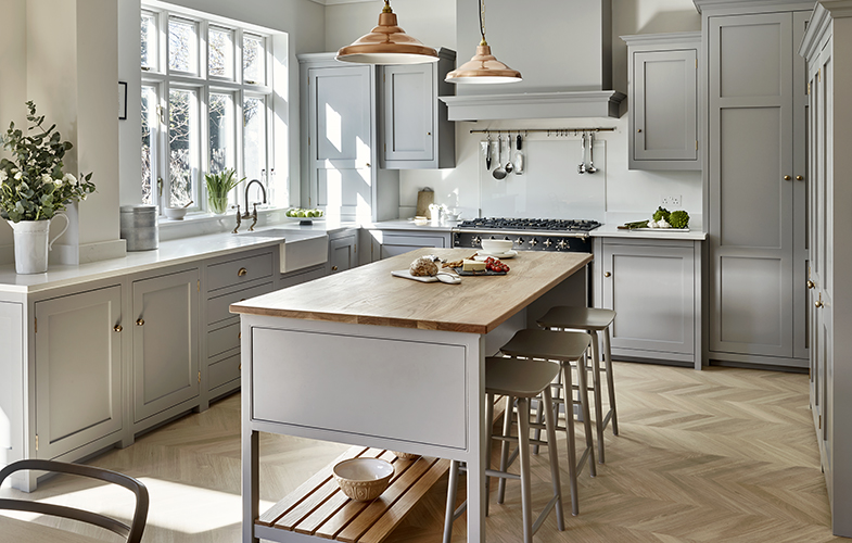 Surbiton Kitchen design with light grey country shaker style cabinets, chevron floor, oak counters and copper island pendant lighting