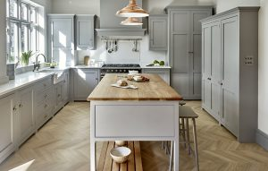 Contemporary country grey kitchen with antique brass handles and oak chevron floors.