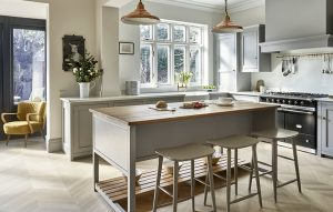 Country kitchen with island. Oak worktop and light parquet floor. Copper pendants and range cooker.