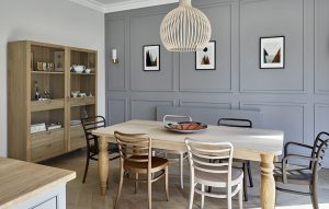 Contemporary dining area with traditional grey paneled wall, solid oak table and parquet flooring.