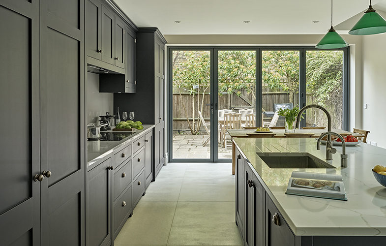 Battersea Black Kitchen. Contemporary shaker style kitchen. Burnished brass handles, grey porcelain floor tiles, Calacatta marble-effect worktops, island with quooker tap and green pendant lighting.