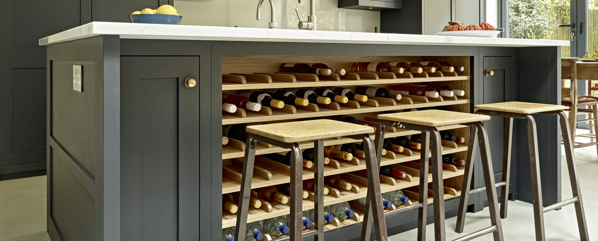 Contemporary country dark kitchen island design with integrated wine rack in light oak