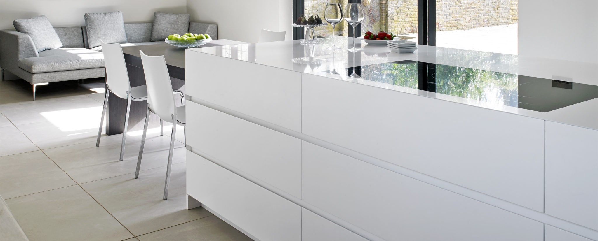 White Contemporary kitchen island with integrated induction hob and dining table - Wimbledon