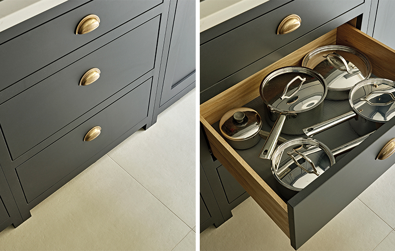 Dark grey painted kitchen island storage drawers with burnished brass handles and oak interior.
