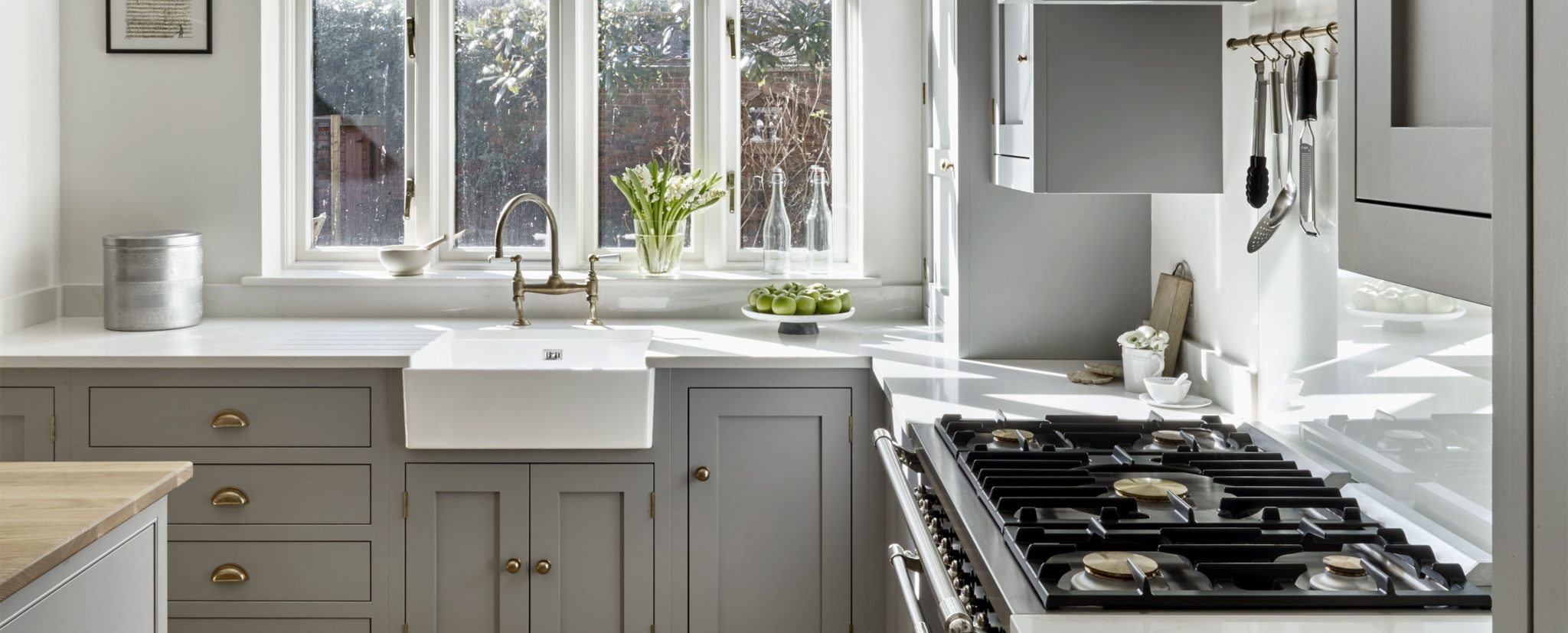Country kitchen Brayer bespoke design with range cooker and butlers' sink. Light blue grey kitchen cabinets with antique brass handles